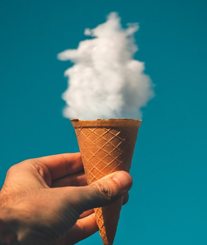 man holding an ice cream with clouds as the background to celebrate ice cream for breakfast day, as part of february marketing calendar