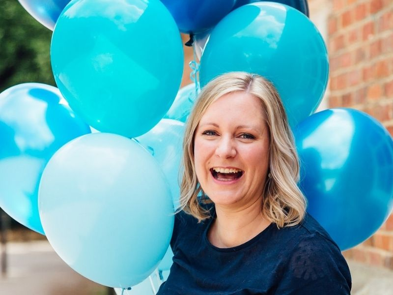 Victoria Prince from Touchpoints Marketing holding some blue balloons